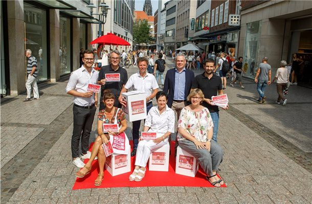 Sie laden ins Quartier ein: Diana Walbröl (Münster Marketing), Petra Pottmeyer (Ludgeriviertel), Ursel Schwanekamp (Pastoralreferentin St. Lamberti; sitzend, v.l.); Christopher Krimphove (Korn und Knierfte), Fritz Schmücker (Münster Marketing), Jürgen Becker (Ludgeriviertel), Andreas Theurich (Centermanager Münster-Arkaden), Linus Weistropp (Quartiersmanager ISI). Foto: Presseamt Münster